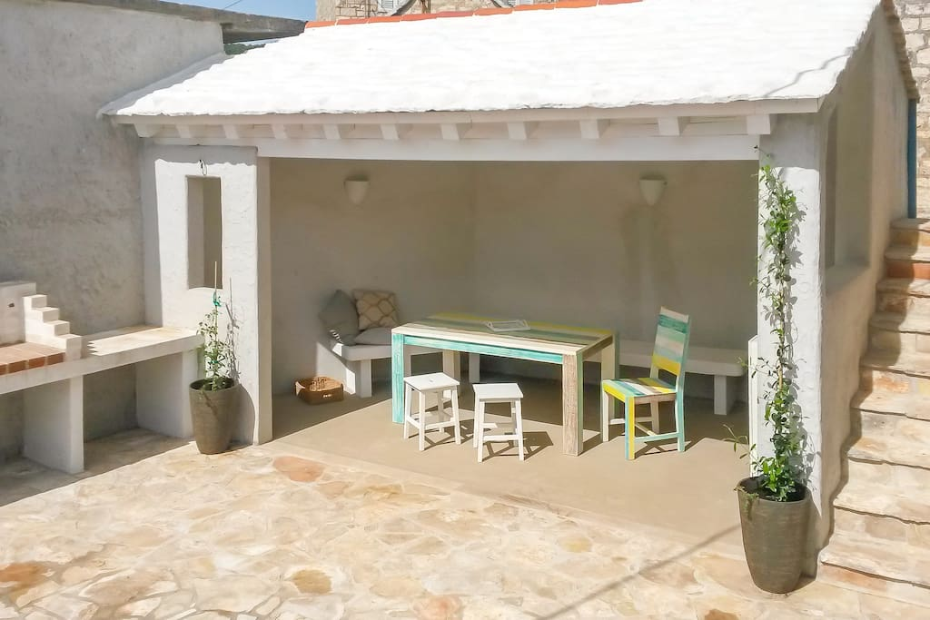 dining outside, bbq, partly roofed patio, small mediterranean herb garden