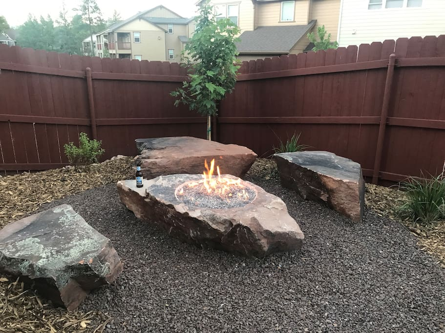 Boulder fire pit in backyard