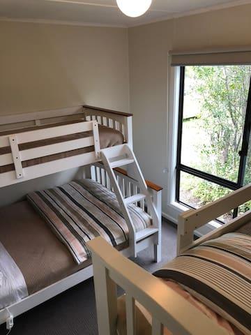 Front bedroom.  Sleeps 5.  1 cozy double bed 3 single beds. ( bunks)
