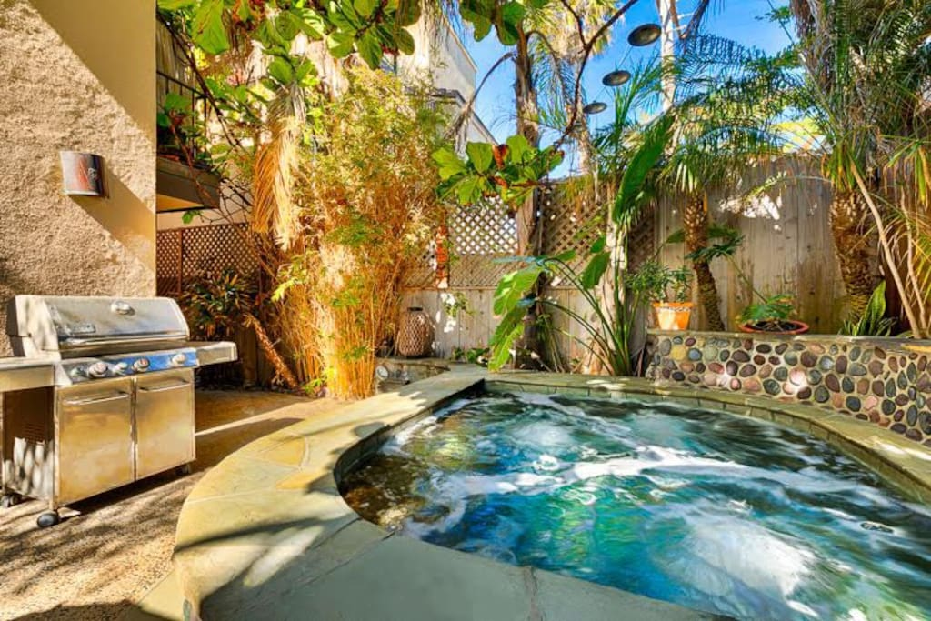 Spectacular hot tun in the backyard's lush tropical landscape. You can almost turn the burgers from the hot tub!