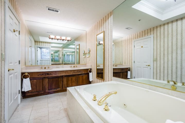 your spacious marble bathroom features a double sink, Jacuzzi tub and separate shower.