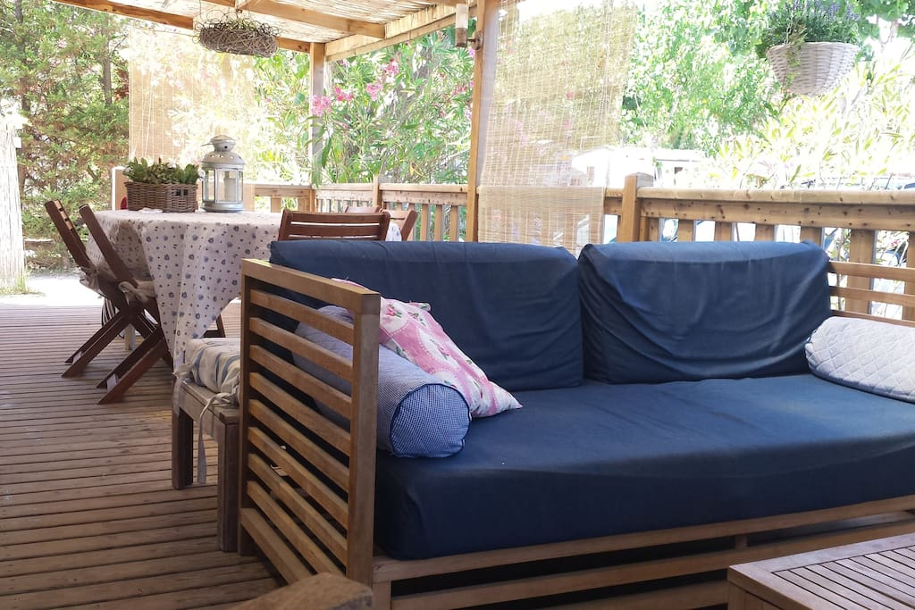 Spacious covered terrace with lounge set, dining table and two wooden loungers with matrasses