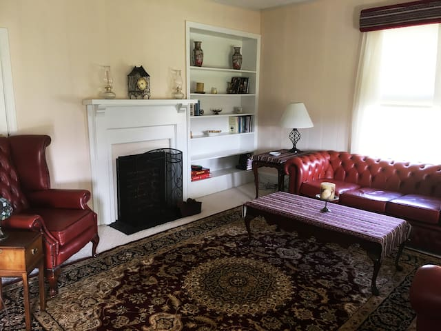 The living room features period-style leather furniture, books and games.