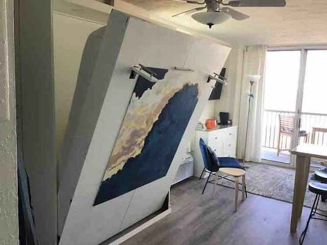 The Murphy bed is behind the painting.
