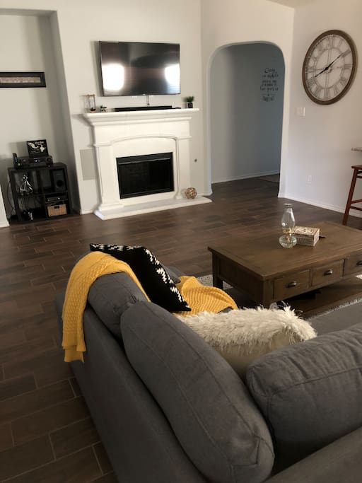 """Living area with big couch and 65"""" smart TV"""