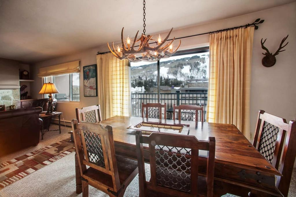 Slope side views at this spacious dining table with seating for 6 and access to the deck with gas grill and plenty of seating.