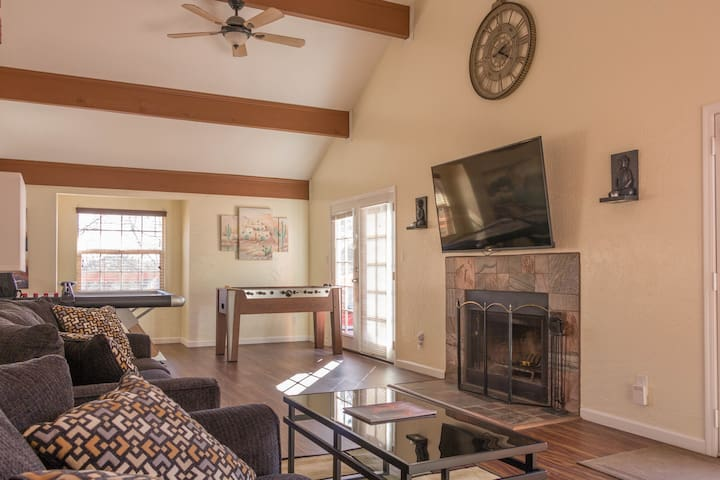 Living room with 65 inch TV and real fireplace.