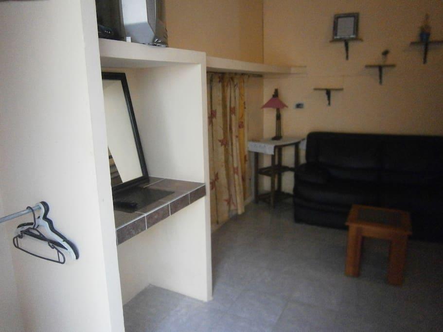 Habitación triple con cama matrimonial e individual, sala con tv/cable.