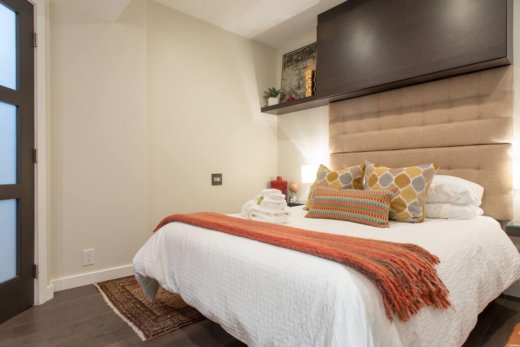 Comfortable queen size bed in a cozy bedroom.