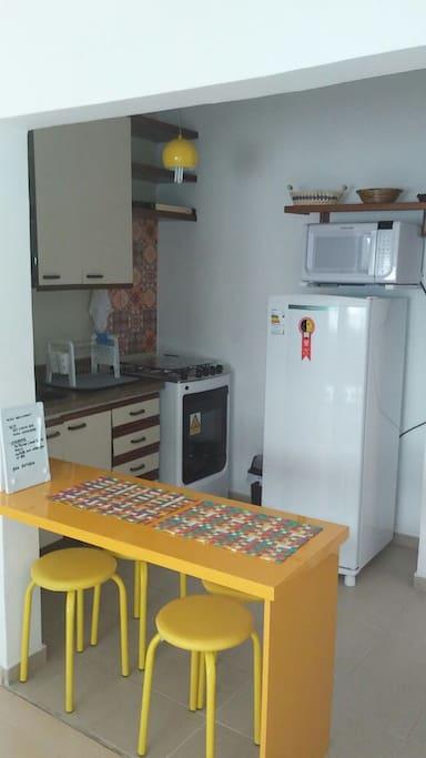 Cozinha americana com fogão, geladeira, micro ondas, cafeteira elétrica e utensílios