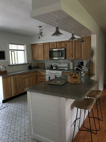 Full Kitchen that includes refrigerator, stove-top/oven, dishwasher, microwave, toaster, coffee maker, pots and pans, dishes, glassware, utensils.  Gorgeous custom concrete counter tops and breakfast bar.  Sliding door to back yard and pool area!