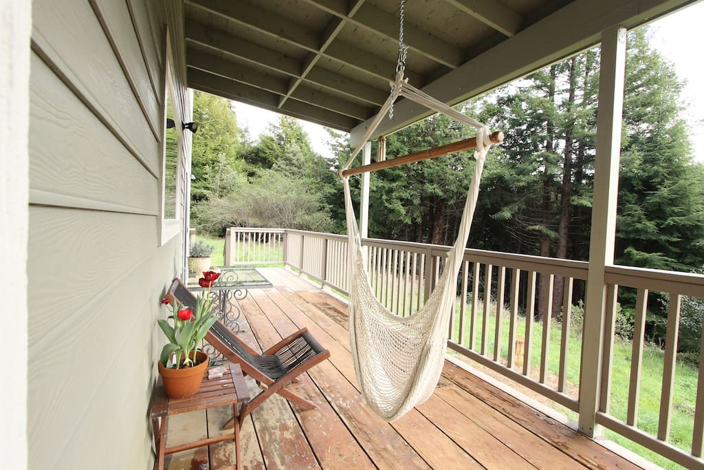 Large back deck with two swinging hammock chairs and  gorgeous views of the redwoods