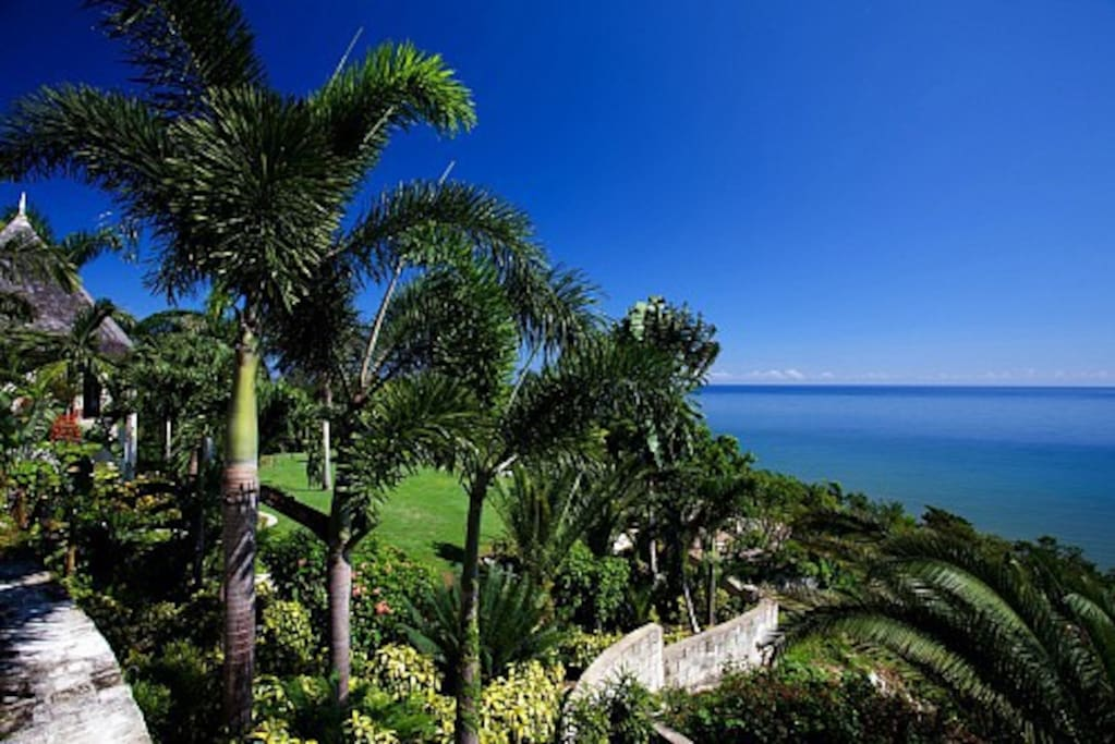 It reigns over a steep hillside. The view of the harbor, passing cruise ships and the town of Montego Bay 12 miles east is an unimpeded sweep of deep blue sea.   Refreshing non-stop trade winds cool the hill and sing through the Royal Palms.