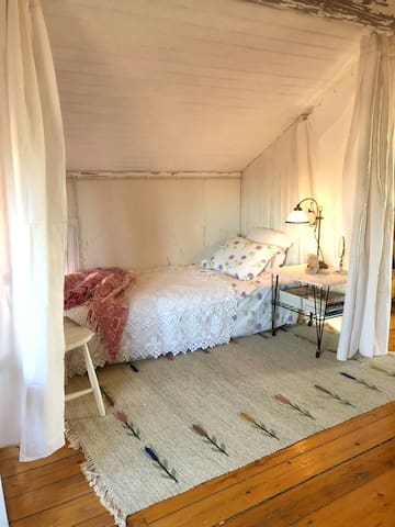 The white room is not actually a room but that does not mean you can't sleep in it! Old beautiful linnen as drapes for privacy.