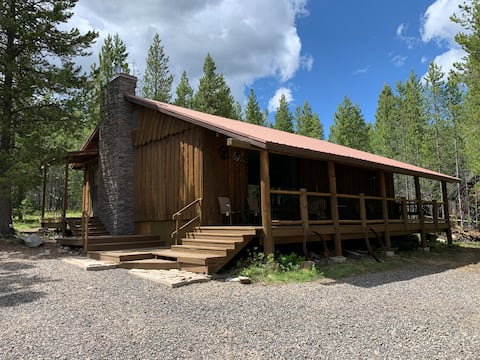 Porch lined cabin nestled in the Pines