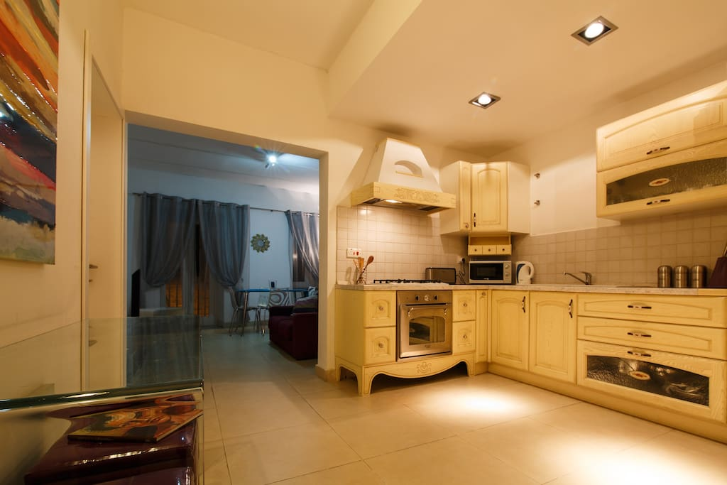 Kitchen with 4 gas hobs, electric oven, microwave & washing machine.