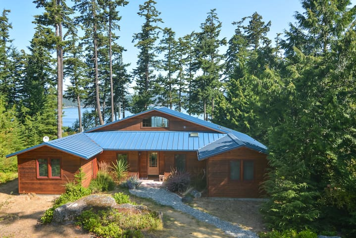 The home is nestled in the trees along the water.   The main entrance to the home can be seen here.