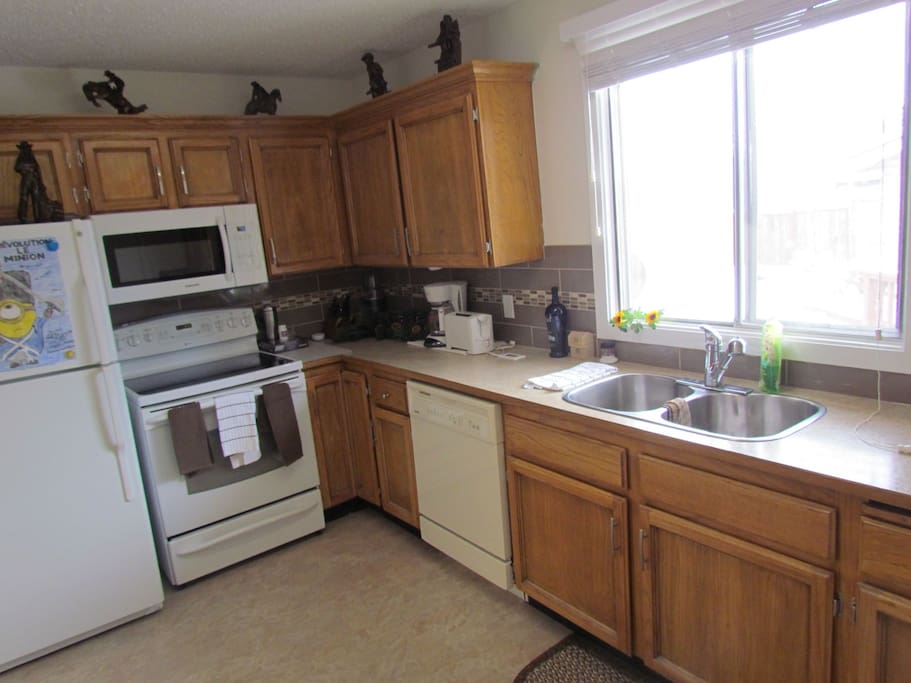 Very nice kitchen with all the pots and pans and dishes and utensils.