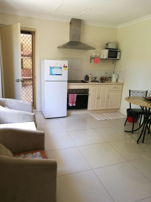 Kitchen and sitting room, with cooking utensils, plates, knives and forks etc..