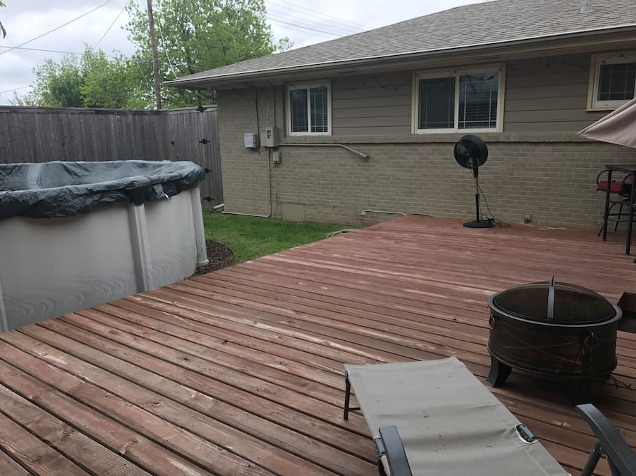 Back deck with tall privacy fence, pool, fire pit, deck furniture and misting fan.