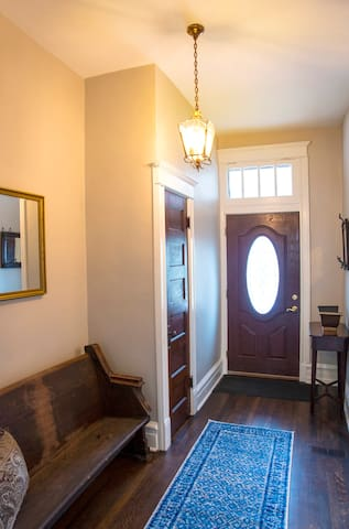 Front Entry with Coat Closet, Original Light, and Vintage Pew from a Historic Church.