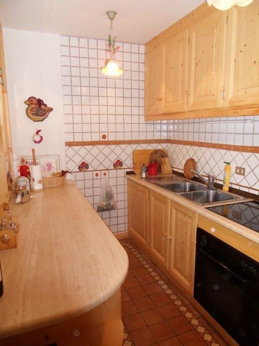 Cucina attigua alla zona pranzo con piano cottura in vetroresina, lavastoviglie e forno elettrico, comodo piano di lavoro in travertino. Dotata di fornita attrezzatura per cucinare.