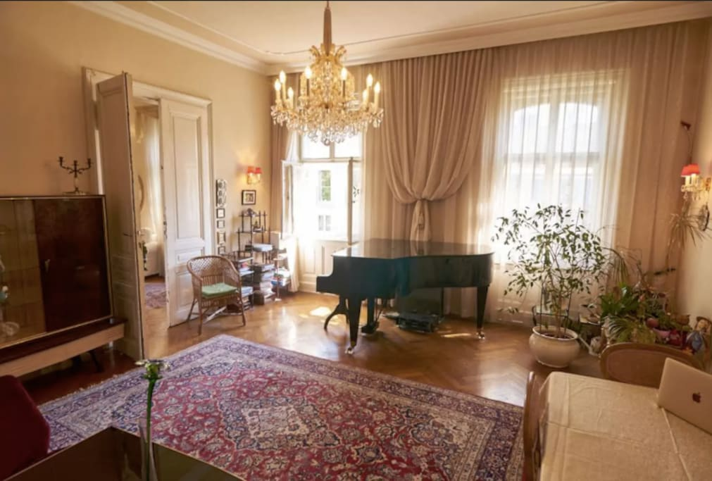 Living room with crystal chandelier,  Boesendorfer grand piano, authentic persian rug, classic viennese accents, and curtains. Perfect place to hangout, read and relax, or practice the piano.