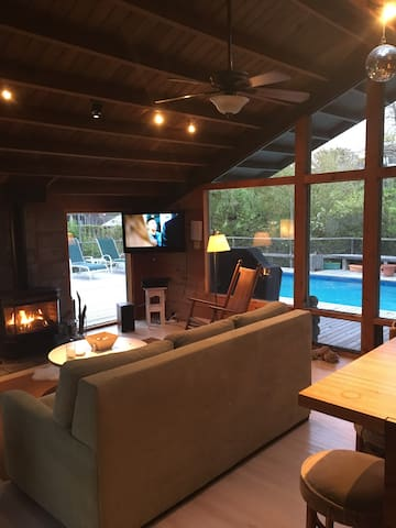 Open concept living space overlooking the pool, deck, and landscaping.