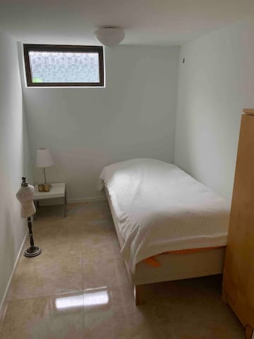 Litet rum med säng i nedersta våningen.