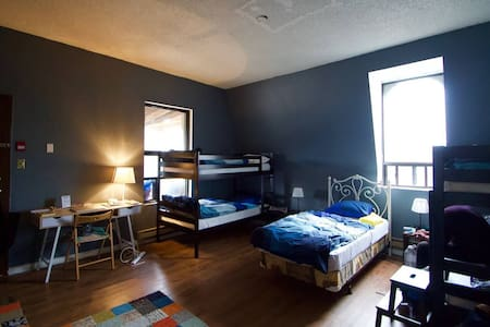 Dorm room has 8 bunk beds, desk, closet and access to outdoor balcony and patio spaces.