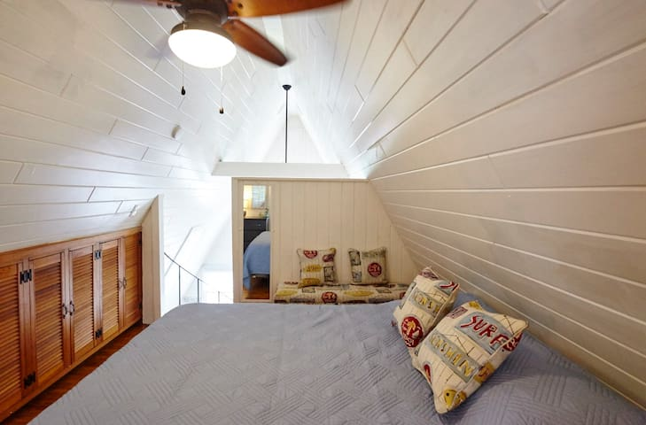 Catch some sleep in the loft bedroom with a queen bed, ceiling fan and window AC unit to keep you cool.