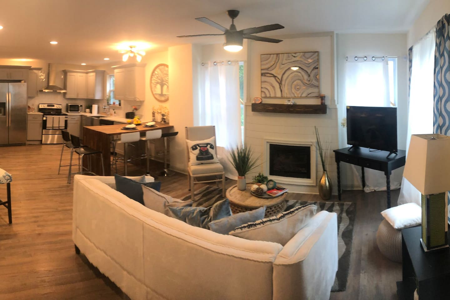 Open floor plan with a cozy fireplace. Featuring modern kitchen with huge farm sink and all stainless steel appliances.