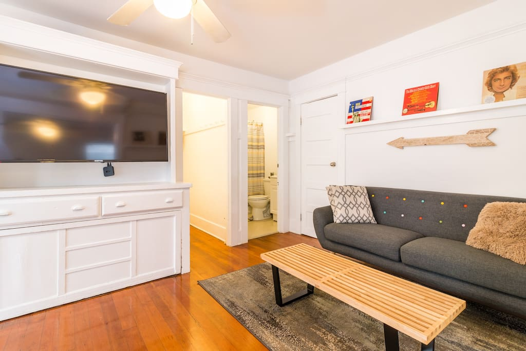 The living area is highlighted by gorgeous wood floors, lots of light, a cozy sofa and large flat screen TV with Apple TV