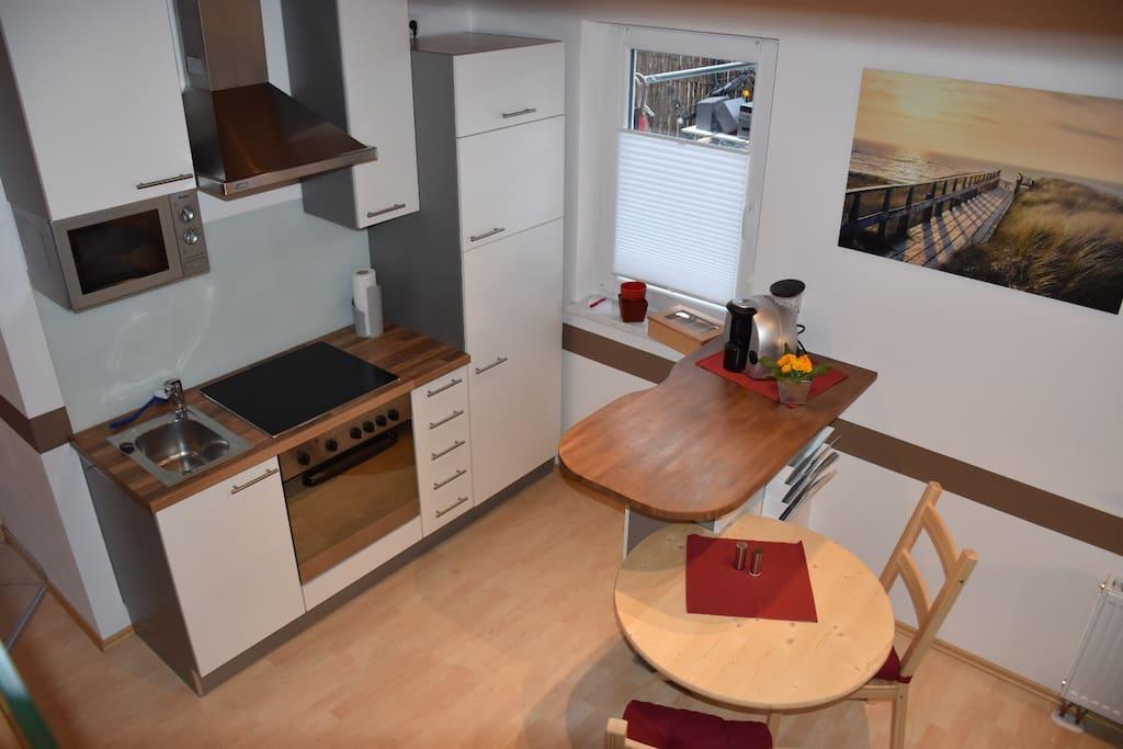 Küche mit Herd, Ofen, Mikrowelle, Kühlschrank/Gefrierfach.