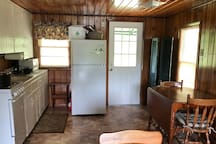 Kitchen with working stove and oven, microwave, fridge and coffeemaker.