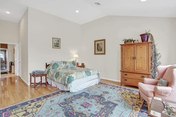 The bedroom includes arm chairs for sitting by the window, as well as solid wood furniture, additional amenities, and unusual plants.
