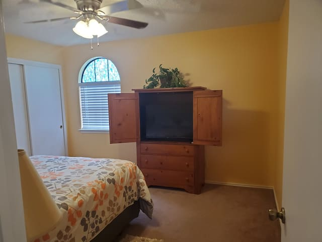 Upstairs bedroom. Queen size bed. Ceiling fan, large smart TV.