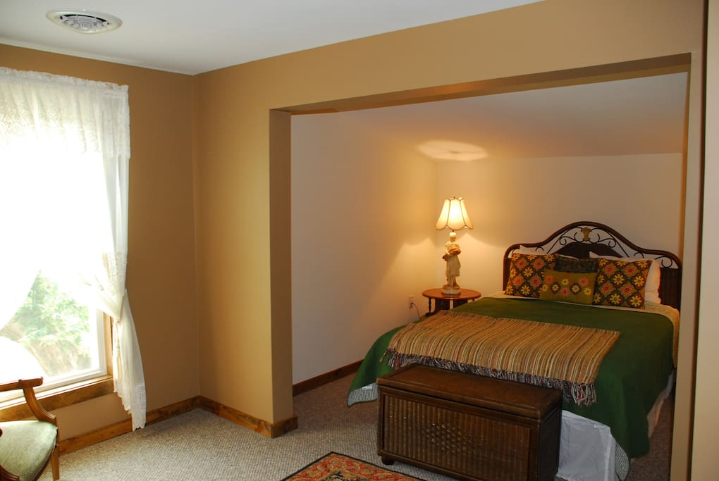 Large bedroom with queen bed and flat screen tv, dvd player, and a selection of movies.