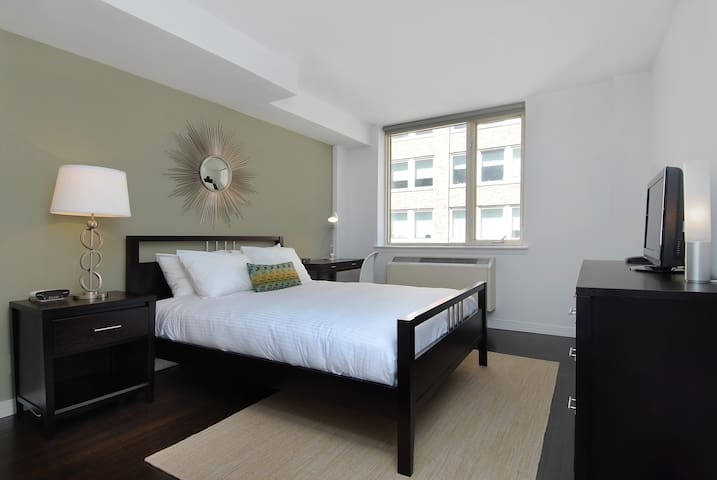 Cozy queen-sized bed fitted with plush linen sheets