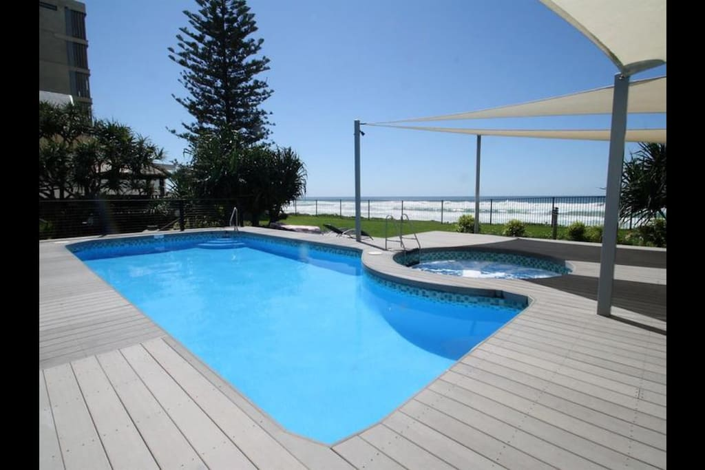 Pool and spa area with lawn leading directly to private beach access