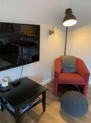 Little reading spot! In the living room area with fireplace, smart 4K TV (+ Netflix) for a cozy night in.   Fauteuil pour lire. Dans le salon avec feu de foyer, télévision intelligente 4K (+ Netflix) pour une soirée tranquille.