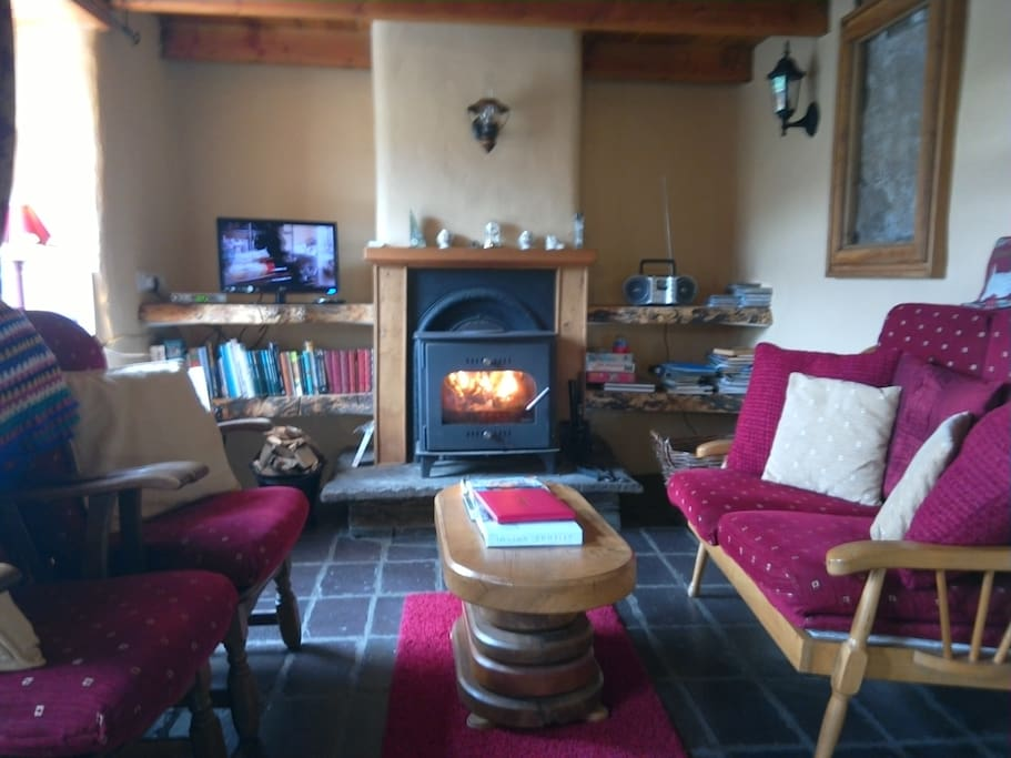 Sitting room in cottage with wood burning stove.