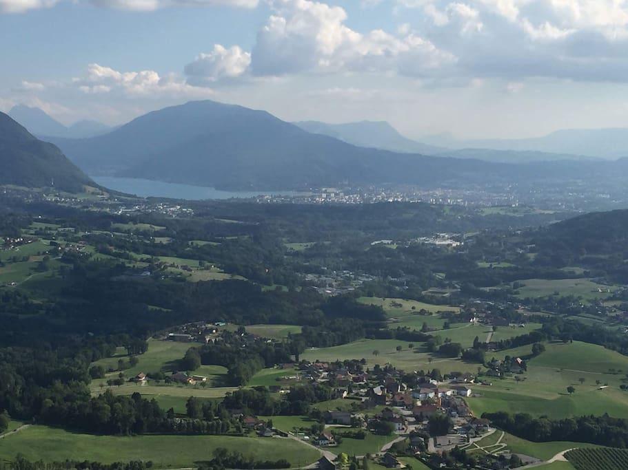 Vue aérienne du village des Ollieres avec la ville d'Annecy et son lac en arrière plan: 12min en voiture