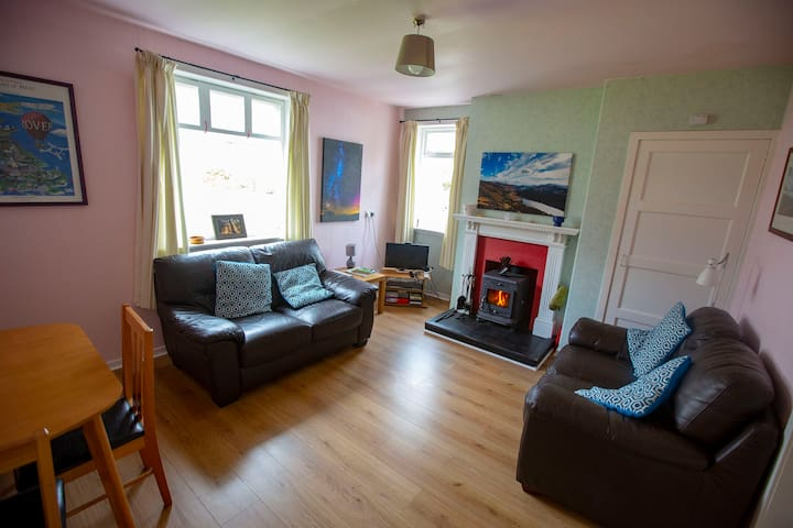 Living room with two sofas, dining table, TV and DVD player, log burner