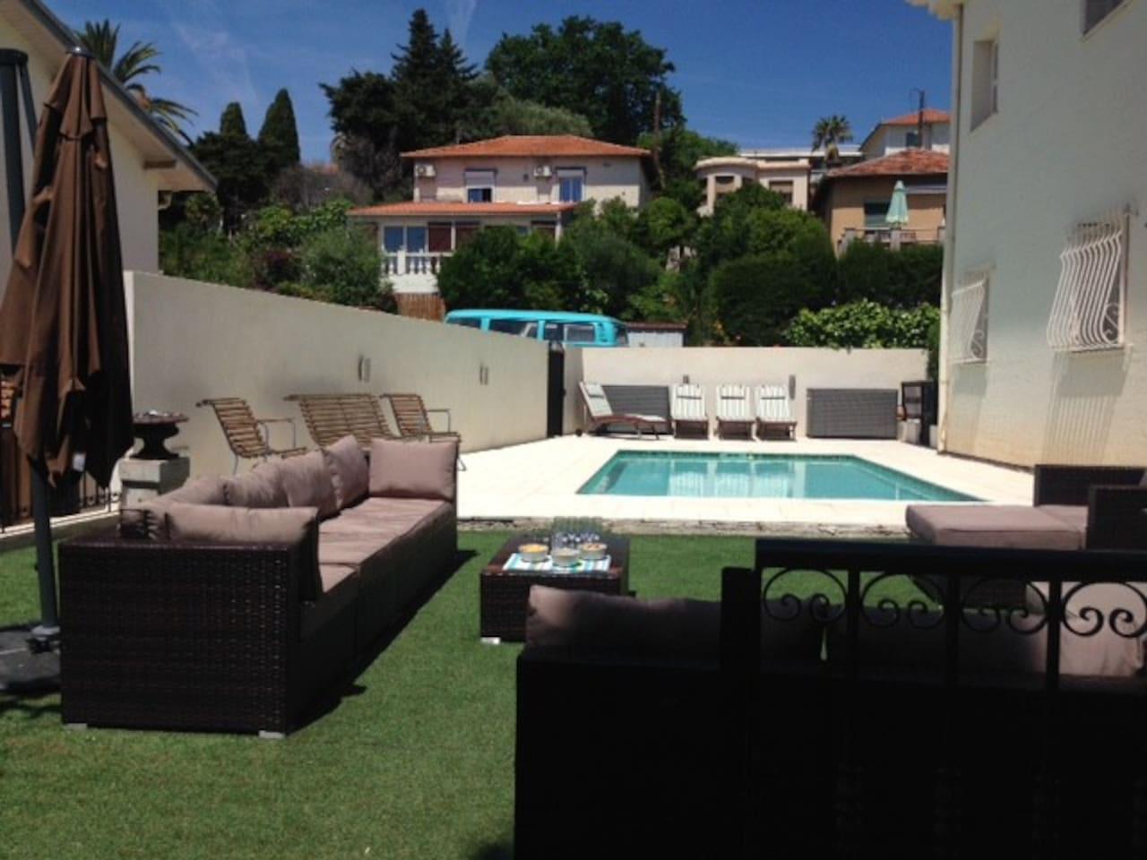 Appartement dans une villa avec piscine et grand salon de jardin.