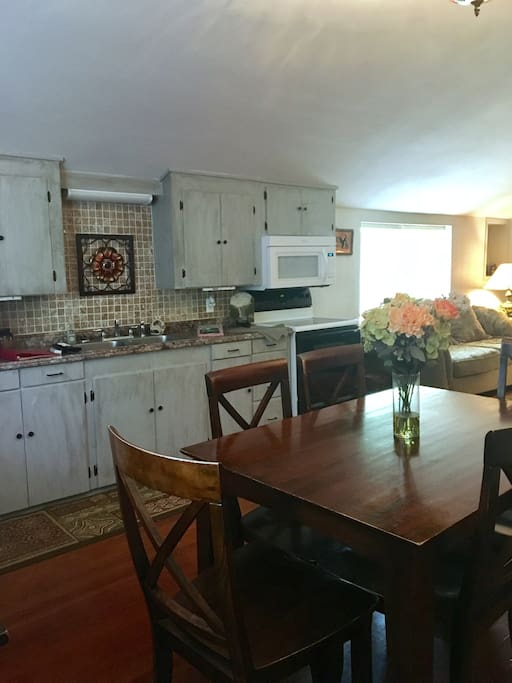 Kitchen with eat-in dining area. Kitchen is equipped with stove, oven, refrigerator, microwave, and Kurig coffee maker and drip coffee maker. Small stock of seasonings in kitchen. Enjoy meals here, along with family time.