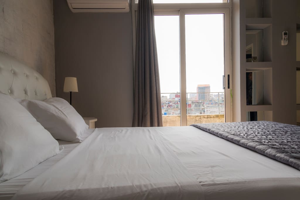 room with queen bed and balcony with beautiful views of the sea and the city
