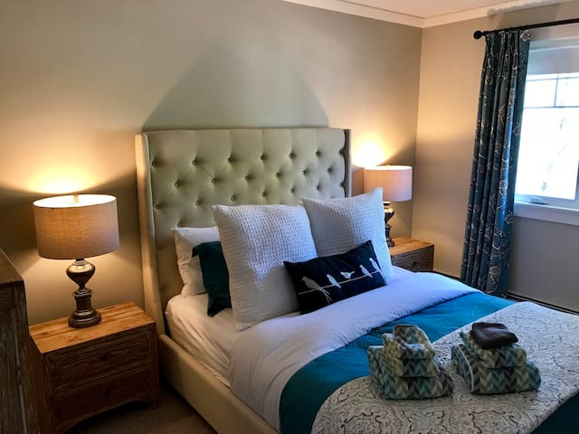 The second bedroom has a hand tufted linen queen bed with premium 100% Pima Cotton 680 thread count bed linens.