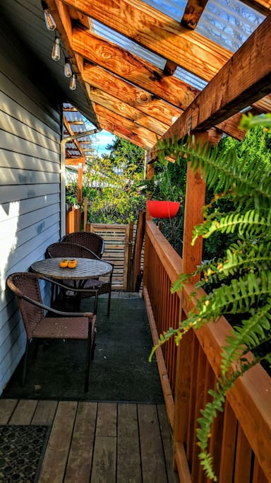 Your entrance and private covered patio deck, in the garden. A clear roof lets you enjoy the Portland rain in comfort. Separately fenced for your pets to enjoy!