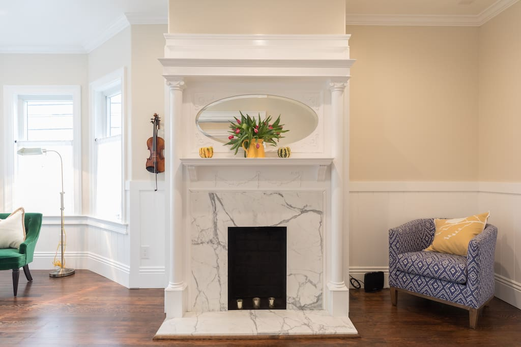 Peaceful, pretty, living room with original fireplace- come and relax after a long day of exploring.